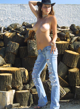 Young busty chick in cowboy hat and jeans