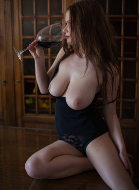 Busty lady drinking wine