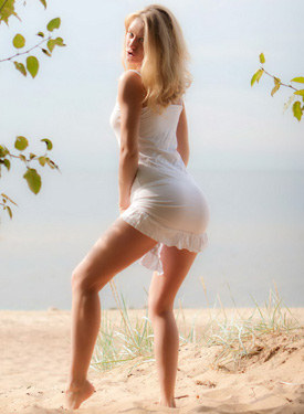Young blonde on the beach in white sexy dress