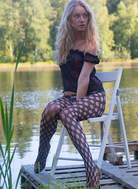 Young lady in net pantyhose at the lake