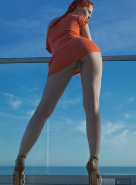 Glamour redhead in orange dress