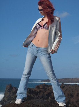 Sexy redhead at the sea in tight blue jeans