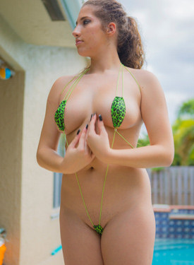 Busty girl is by the pool in green micro bikini