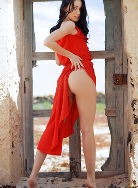 Exciting girl wearing sexy red dress has got erected nipples in old ruined house