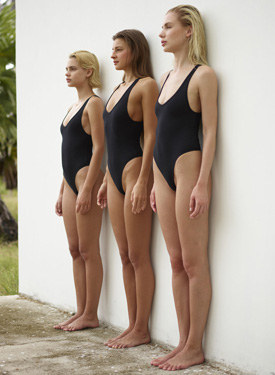 Three girls in black swimsuits photo wall shots at the nature