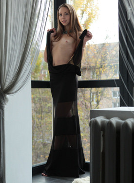 Young girl in long sexy fashion black dress undresses by the window to show her exciting fresh slim body with the nipples stretching and large pussy lips